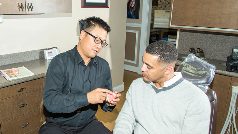 Dr. Michael Chung consults with a patient at his dental office in Virginia