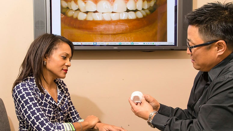 Dr. Michael Chung shows a patient a dental mold during a consultation