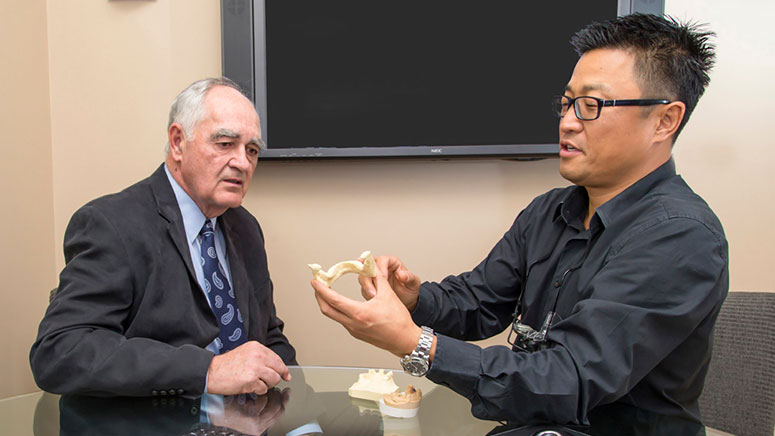 Cosmetic dentist Dr. Michael Chung consults with a patient